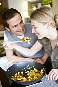 Young couple tasting vegetables cooked in wok