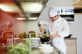 Young chef cooking vegetables in wok