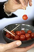 Cocktail tomatoes on cocktail sticks in a small bowl