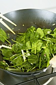 Sweating spinach in a wok