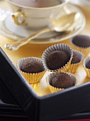 Chocolate truffles beside a teacup and saucer