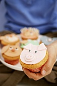 Hand holding muffin with pig's face