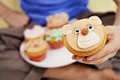 Hand holding muffin with bear's face