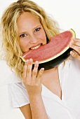 Blond woman biting into a slice of watermelon