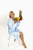 Woman sitting on a chair with a bowl of fruit in her hands