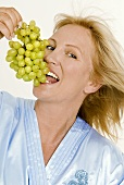 Blond woman eating grapes