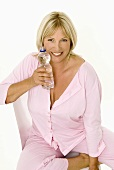 Woman sitting on a chair with a bottle of mineral water