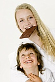 Girl biting into a bar of chocolate, boy in front