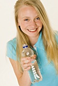 Blond girl holding a bottle of mineral water in her hand