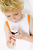 Small boy eating a chocolate-covered marshmallow wafer