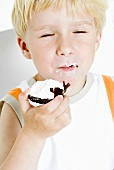Blond boy enjoying a chocolate-covered marshmallow wafer