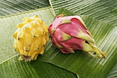 Yellow and pink pitahayas on banana leaves