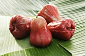 Four red Java apples on banana leaves