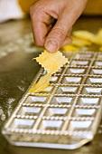Taking home-made ravioli out of ravioli tray