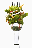Green ribbon pasta with vegetables and sauce on a fork