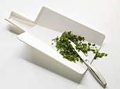 Chopped herbs on a flexible chopping board