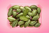 Baby cucumbers in a plastic container