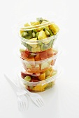 Mixed fruit salad in three plastic containers