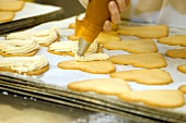 Piping cream onto biscuits