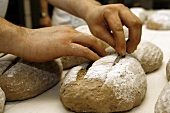 Slashing the top of shaped loaves of bread