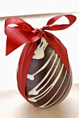 A chocolate Easter egg with a red bow