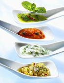 Four chutneys and relishes on small spoons