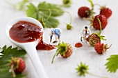 Two little toy men among wild strawberries and jam