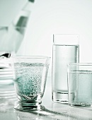 Three glasses of mineral water with bottle in background