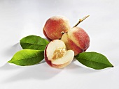 Two whole peaches and part of a peach with twig and leaves