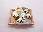 Cup of coffee and small cakes on tray