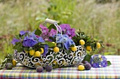 Hydrangeas, damsons and mirabelles in a wire basket