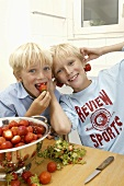 Two blond boys hulling strawberries