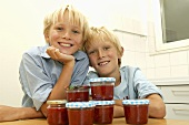 Two blond boys with jars of strawberry jam