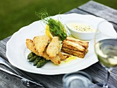 Fried fish in batter on green asparagus with tower of chips & dip