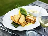 Backfisch auf grünem Spargel mit Pommes frites-Turm und Dip