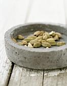 Cardamom pods in stone dish