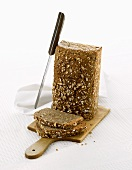 A wholemeal loaf, standing on its end, with knife