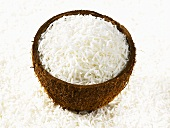 Grated coconut in half coconut shell surrounded by grated coconut
