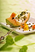 Quark on a melon wedge with pistachios and flaked almonds