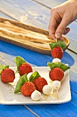 Hand reaching for strawberry and mozzarella skewer