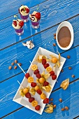 Skewered fruit with chocolate sauce, fruit compote with cherries