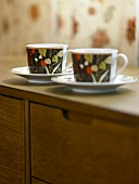Two cups and saucers on a sideboard