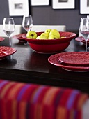 Bowl of apples on table with red tableware