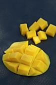 A mango half cut into cubes and cubes of mango
