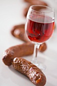 A glass of red wine surrounded by sausages