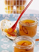 Two jars of apricot and chilli jam with spoon