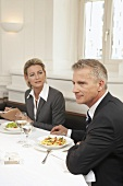 Two business people holding a meeting over a meal