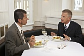 Two men having a discussion over lunch in a restaurant