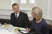 Businessman speaking to secretary over meal in restaurant