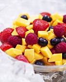A bowl of mango and mixed berry salad with vodka on ice